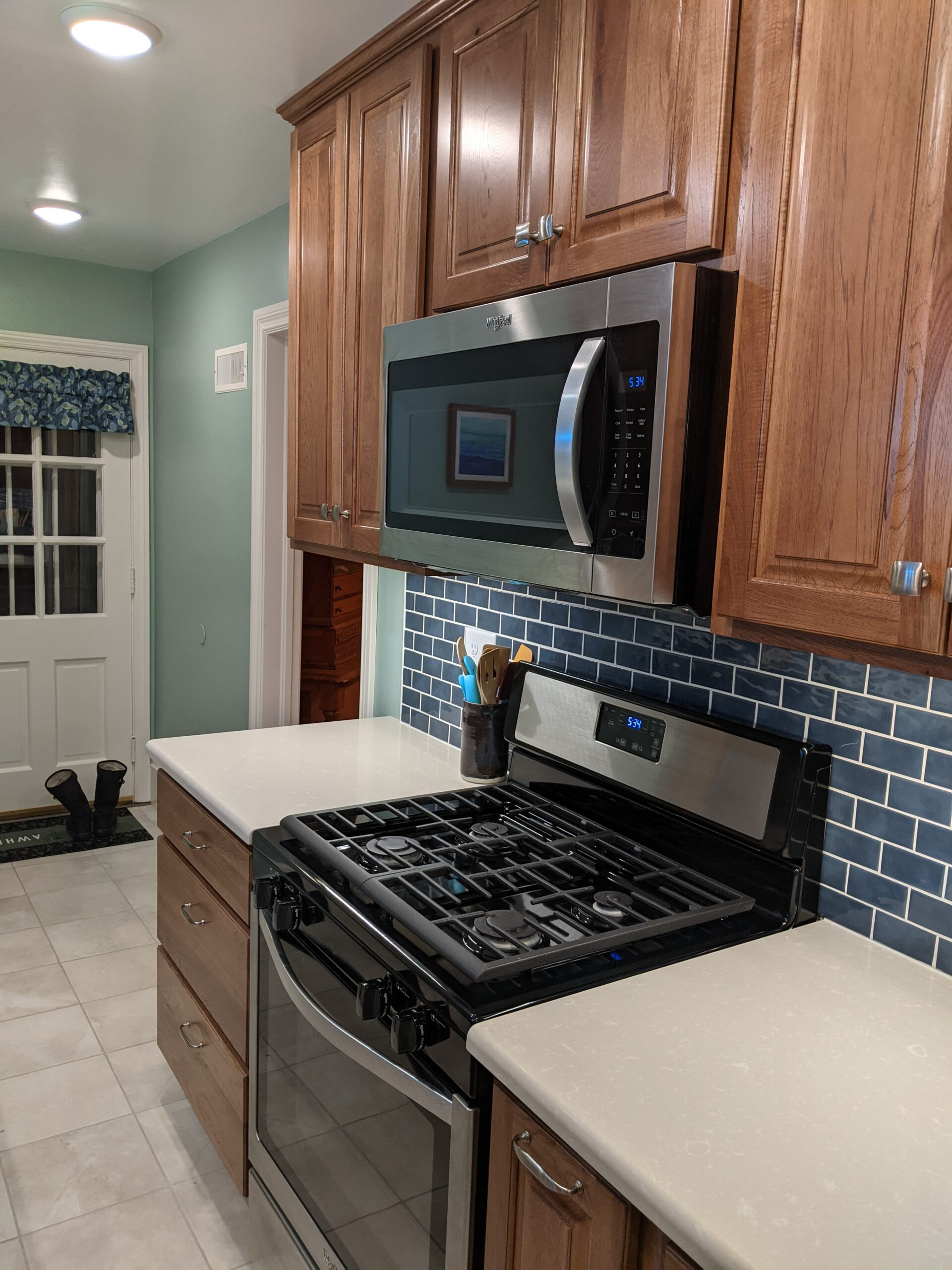Shows the new stove area with the tiled backsplash and countertop space around the stove