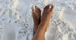 Two brown adult feet crossed over each other in the white sand