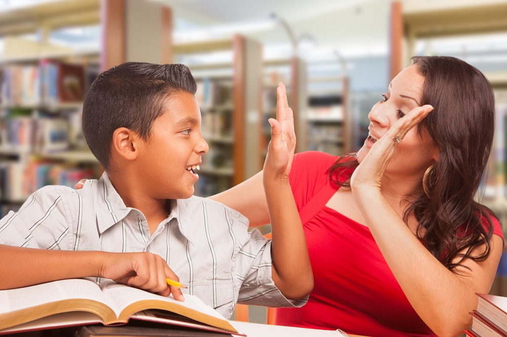 Helicopter parent Mom high fives son while studying in library