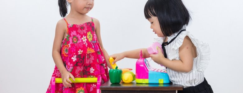 Two young girls playing shop as one of many fun money activities for kids