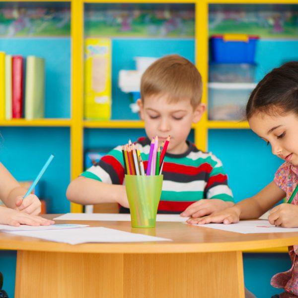 Three cute preschool children drawing at daycare