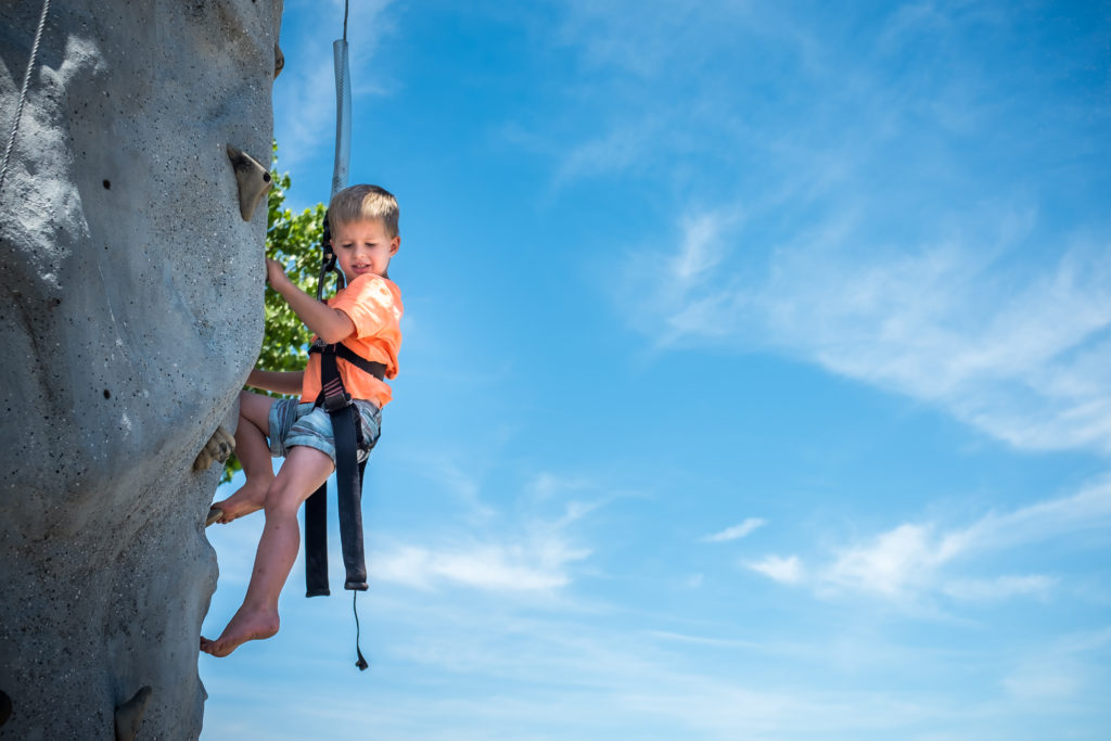 little boy child climbing a rock wall