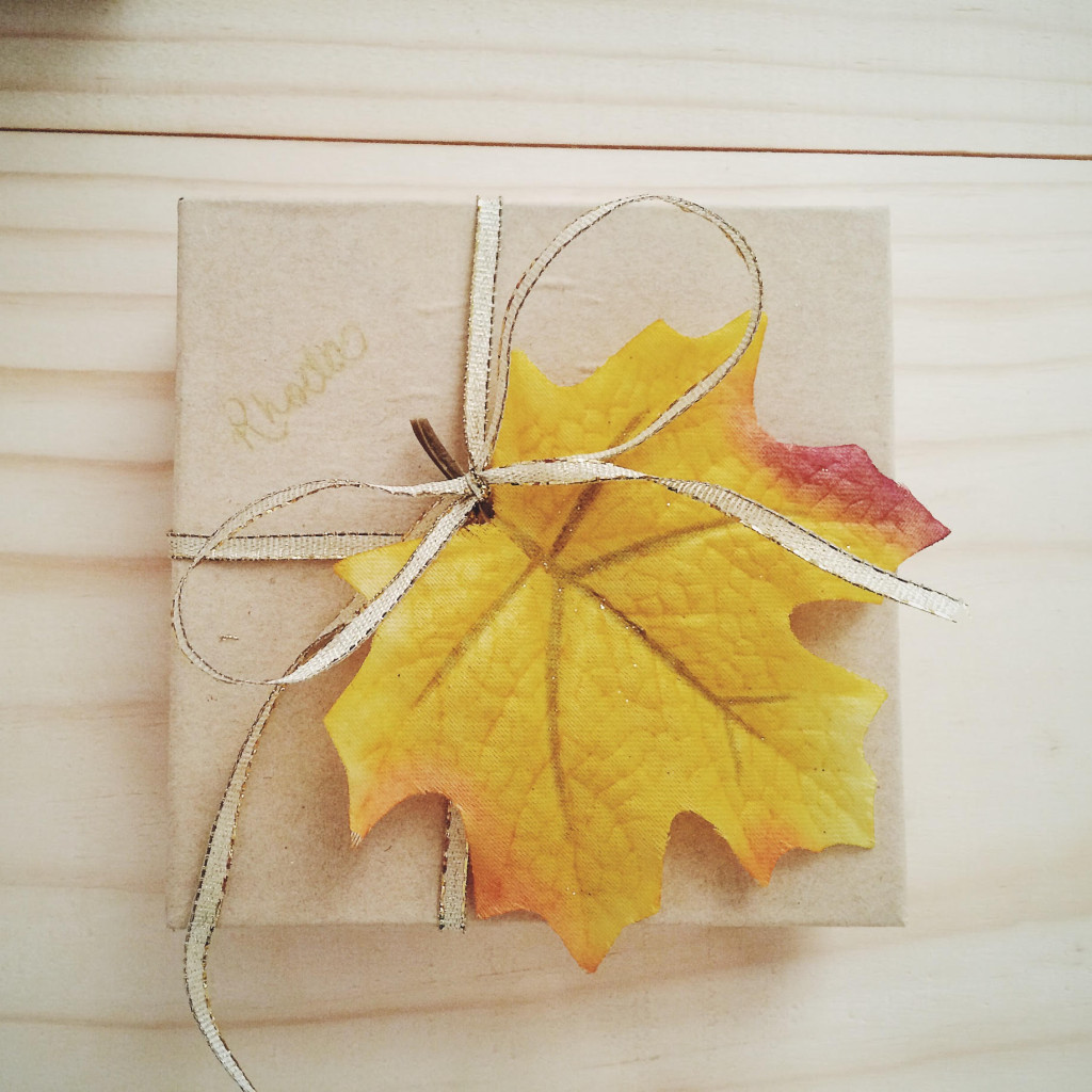 Small brown paper box tied with gold ribbon and golden yellow leaf on top