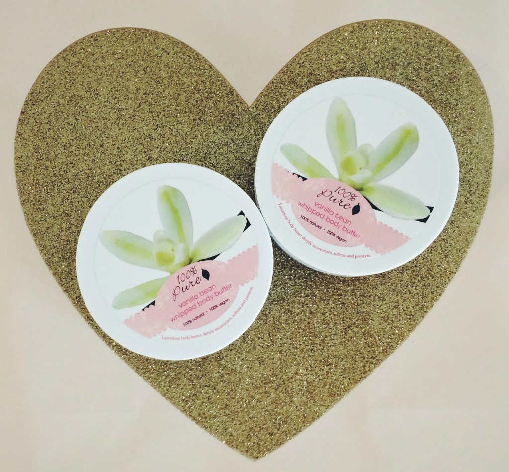 Tubs of 100 percent pure vanilla bean whipped body butter on top of blush and gold heart gift bag
