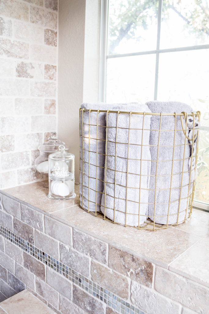 glass apothecary jars and gold basket with grey towels in master bathroom