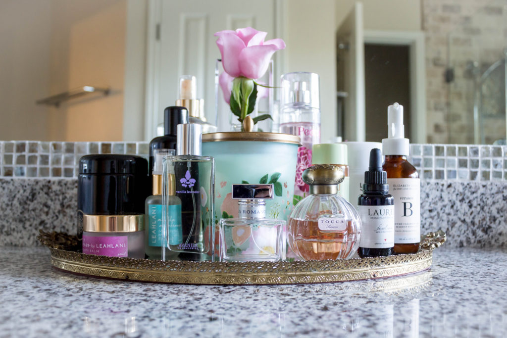 gold vanity tray with skincare and perfume in master bathroom