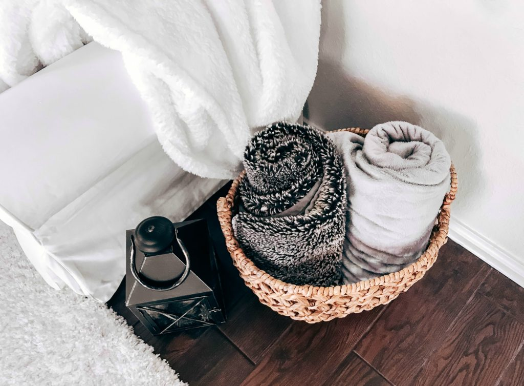 basket of rolled up soft and cozy blankets by couch