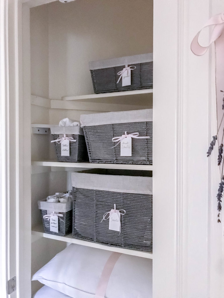 inside view of linen closet with grey baskets