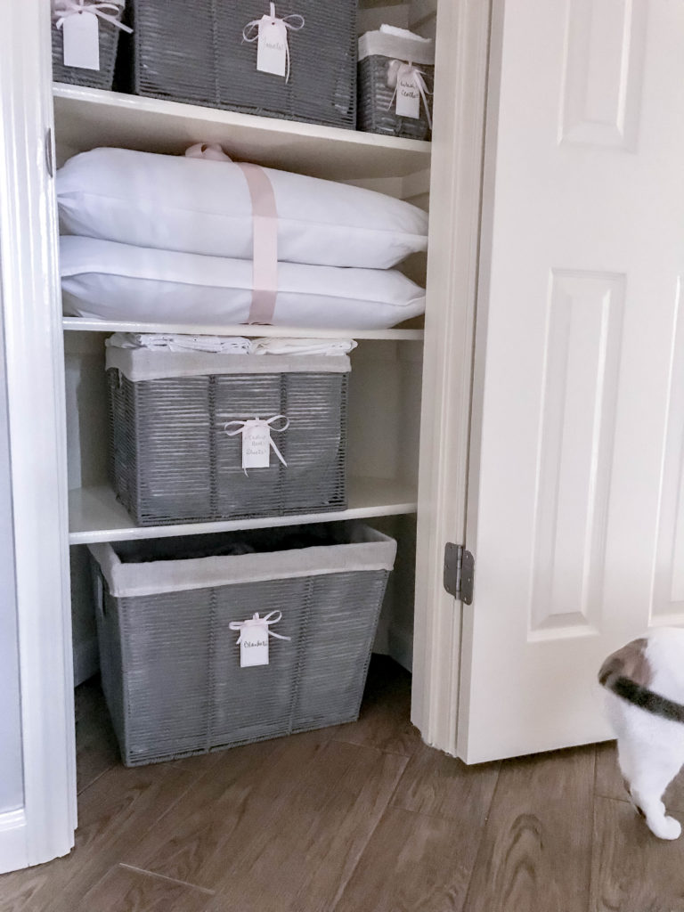 inside view of linen closet with baskets and cat tail in the shot