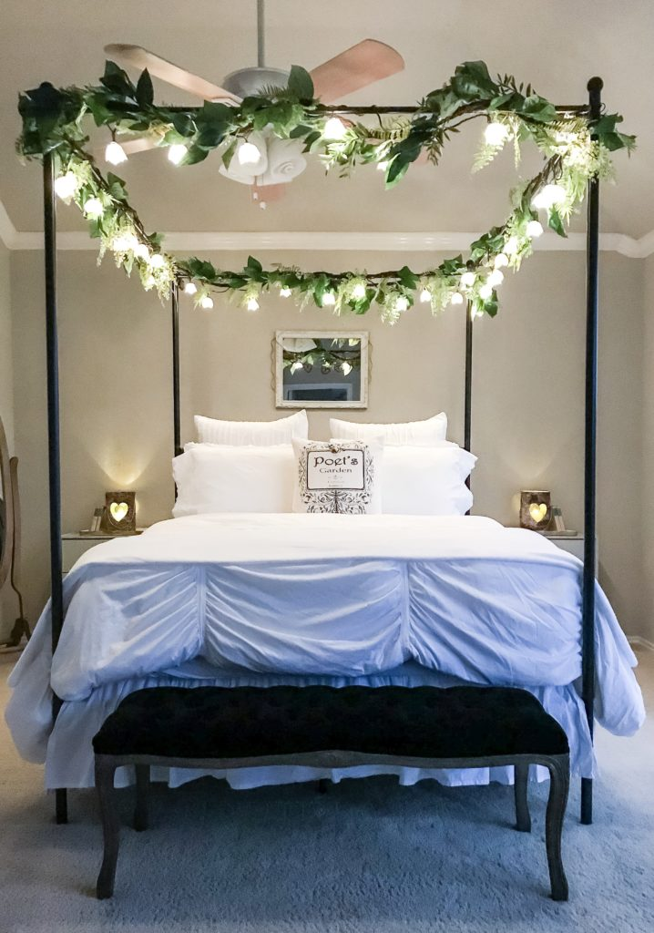 night time view of canopy bed with garlands and fairy lights on top