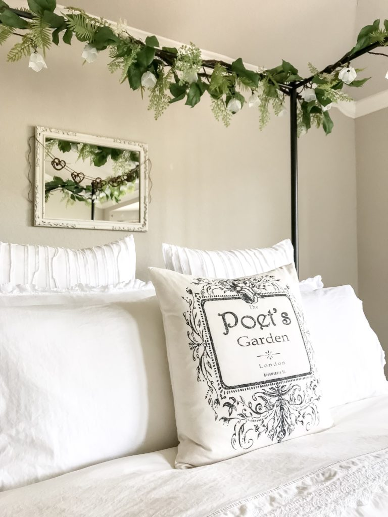 toss pillow that says poet's garden, white mirror with heart garland and green garlands at top of canopy bed