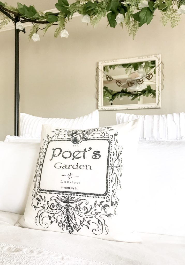 view of front of bed with pillow that says poet's garden and white mirror with heart garland