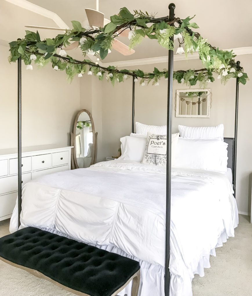 full side view of black canopy bed with white bedding and garlands on top