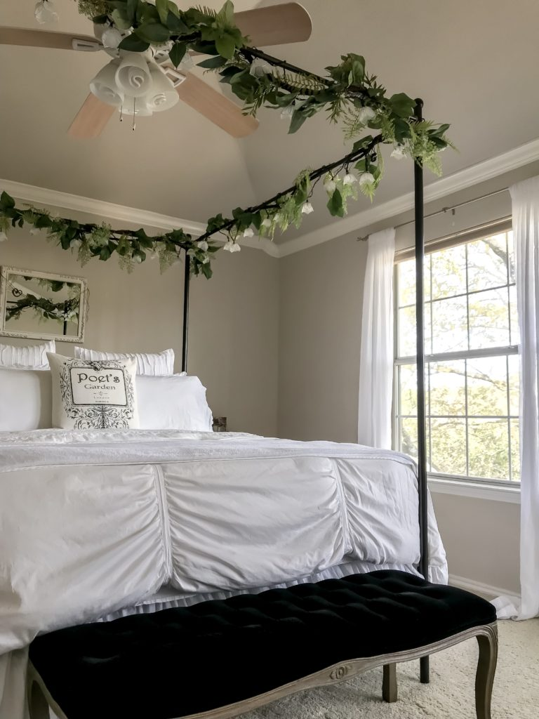 Canopy bed with garlands and view of bedroom window