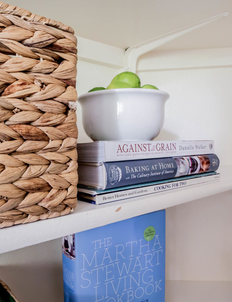 cookbooks stacked and bowl of limes on top