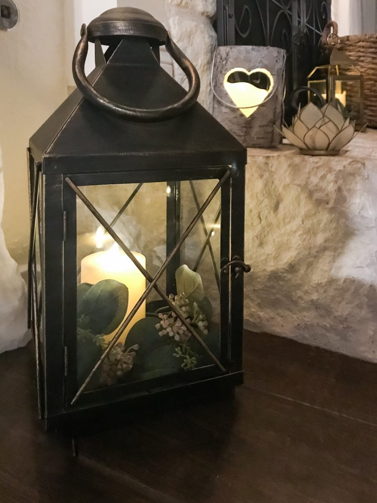 black iron lantern with candle and faux greenery inside