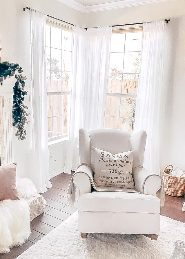 sheer white curtains on windows behind white rocking chair