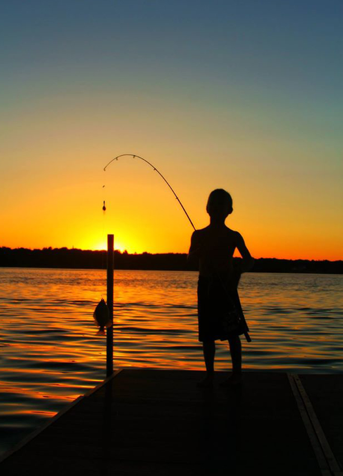 Boy fishing from dock at sunset