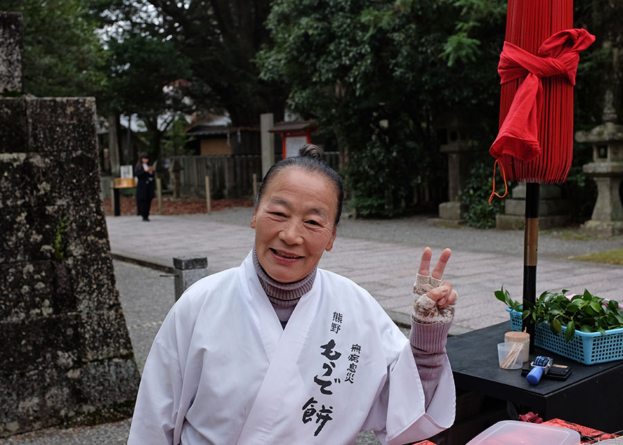 A woman selling snacks outside Hayatama Taisha