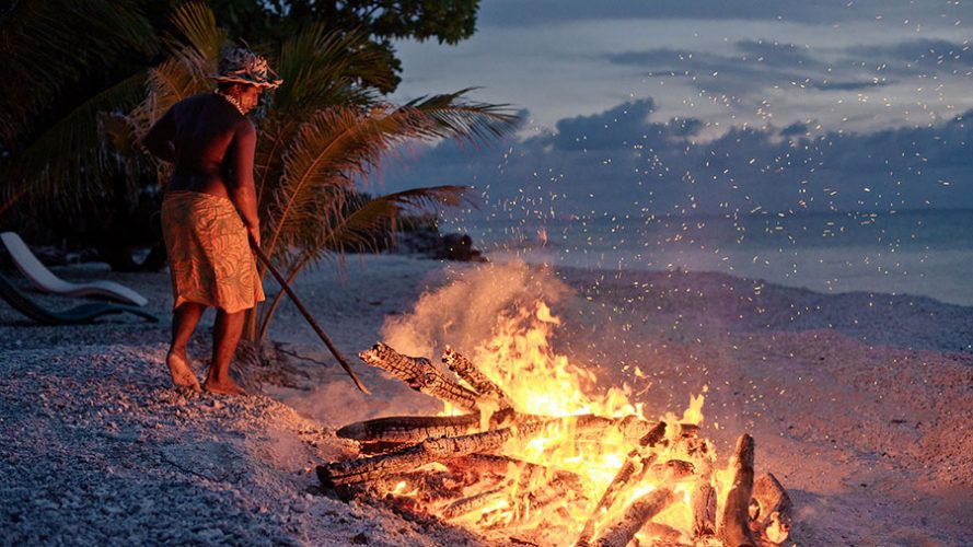 A man stoking a fire on the beach. Rangiroa. Credit: Hélène Havard / Tahiti Tourisme