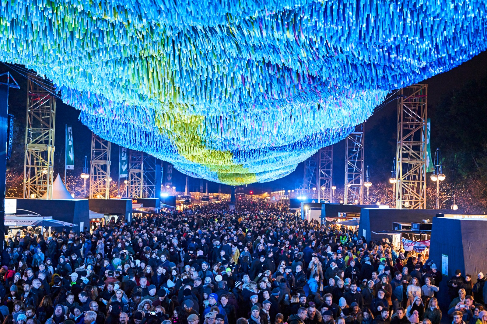Crowd of people under Visions in Motion by Patrick Shearn lit up at night