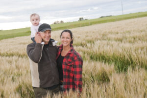 Young family in a field with a baby.