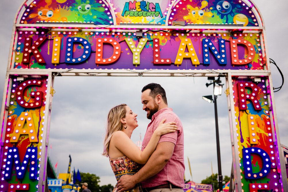 Bride and Groom smiling by the Kiddyland rides at the Ohio State Fair
