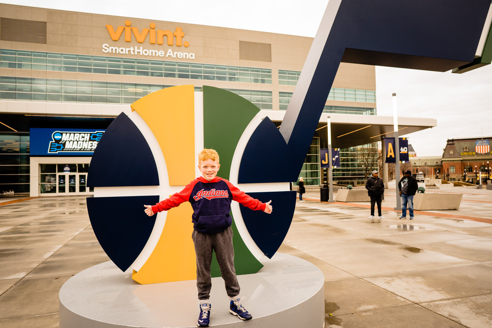 Planning your epic Utah family vacation. Young boy standing outside the Vivint stadium where the Utah Jazz play