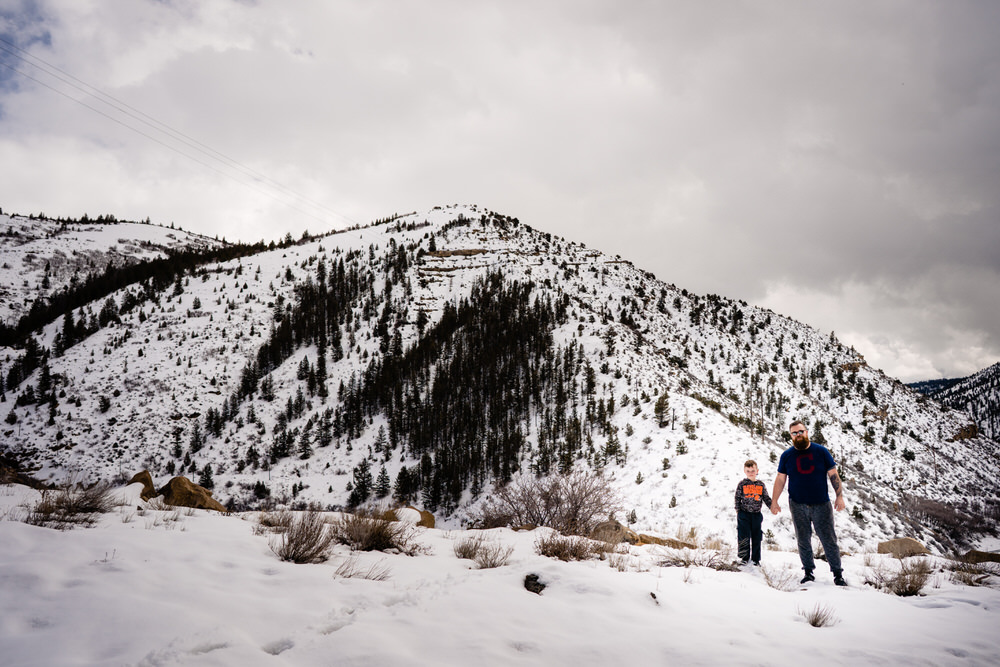 Planning your epic Utah family vacation. Dad and son stand in snowy Utah outside of Moab Utah