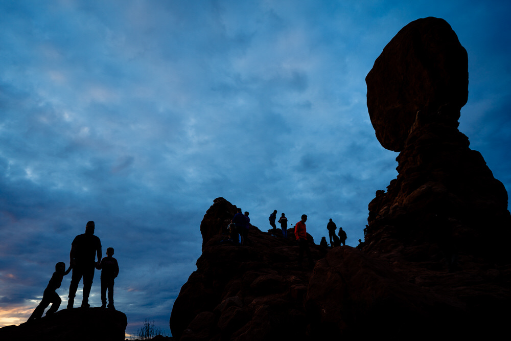 Planning your epic Utah family vacation. Family play on the trails of Arches National Park.