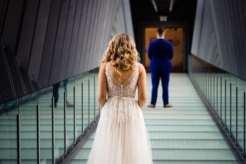 A bride walks across the Columbus Downtown Hilton skywalk in Columbus, Ohio to see her groom for a first look.