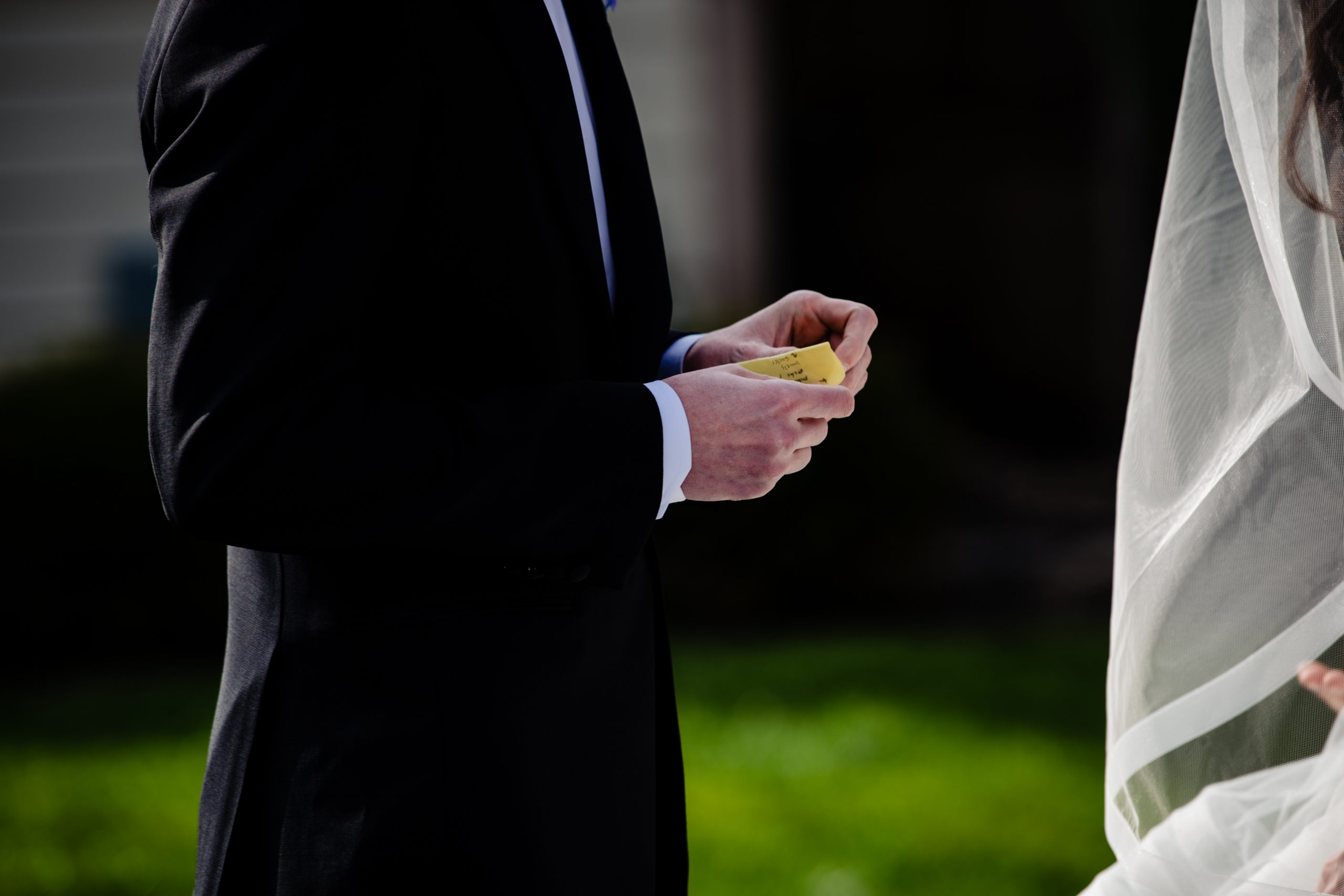 A groom holds his vows as he listens to his bride reads her during a COVID ceremony in Columbus, Ohio.