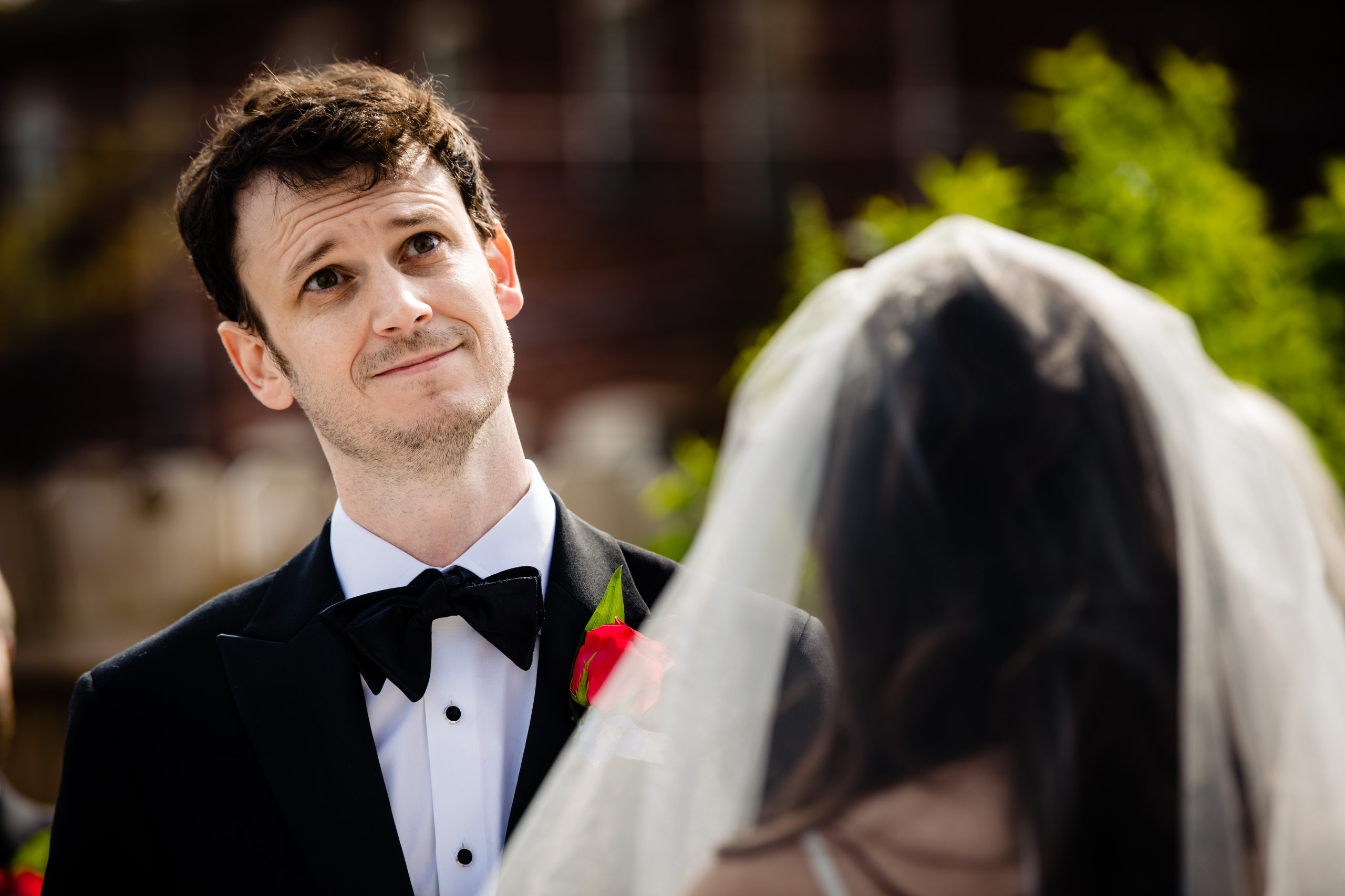 A groom listens to his bride read her vows during a COVID ceremony in Columbus, Ohio