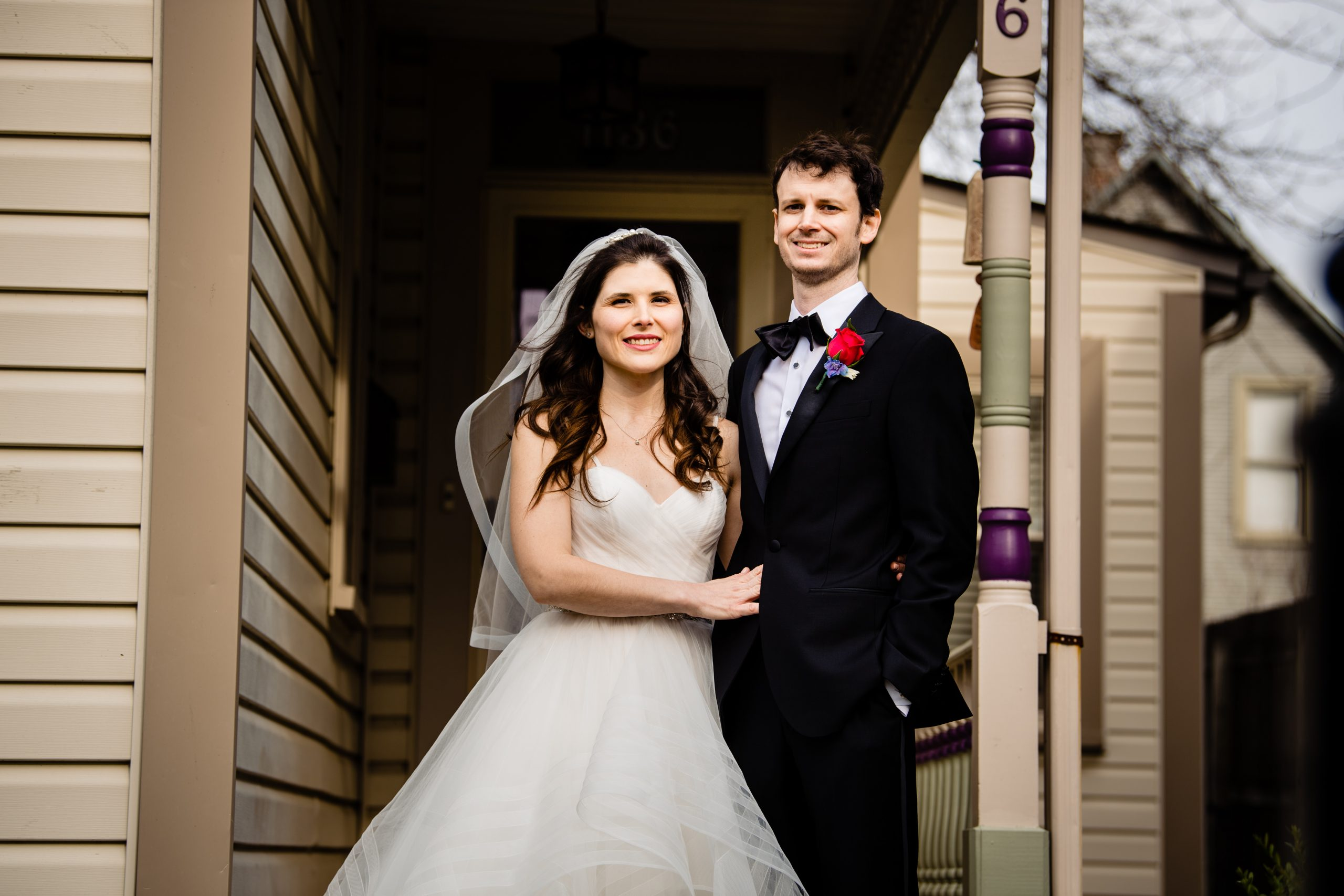 A bride and groom outside of their home after their COVID ceremony.
