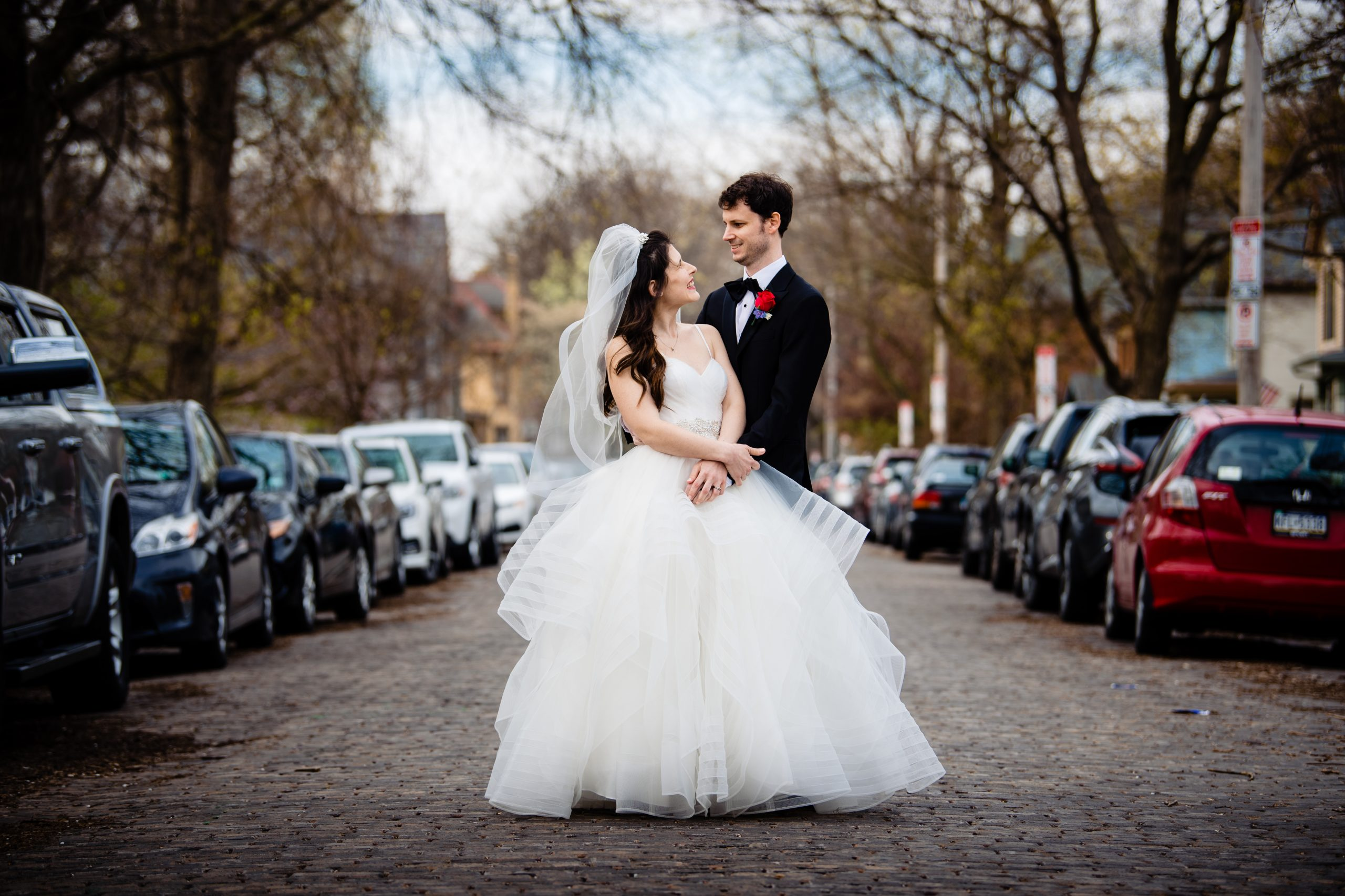 A bride and groom standing in the street on their wedding day