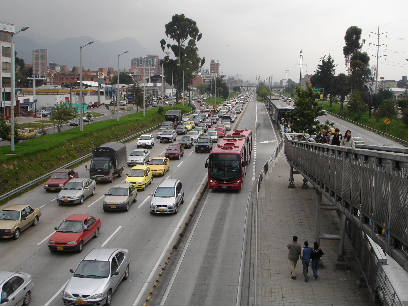 """Bogotá: Double lanes at stops permit express buses to pass at stations while """"bendy"""" articulated buses allow greater passenger capacity per bus. Passengers access stations via walkways which bridge highways."""