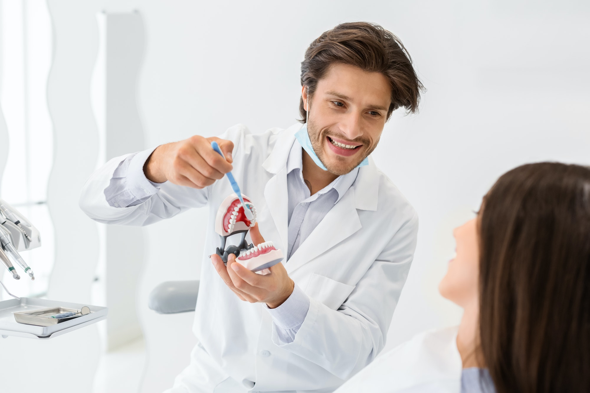 Cheerful doctor showing how to brush teeth using jaw model