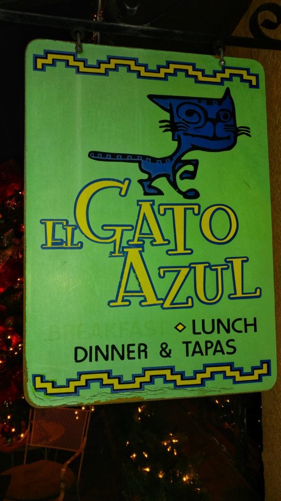 Outdoor signage for El Gato Azul, a casual creek side cafe serving tapas and homemade desserts.