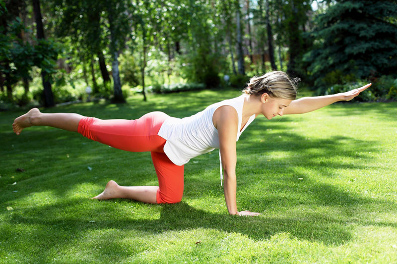 Yogini wearing mid-calf yoga pants doing yoga in the park