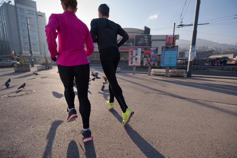 man and woman running in urban setting