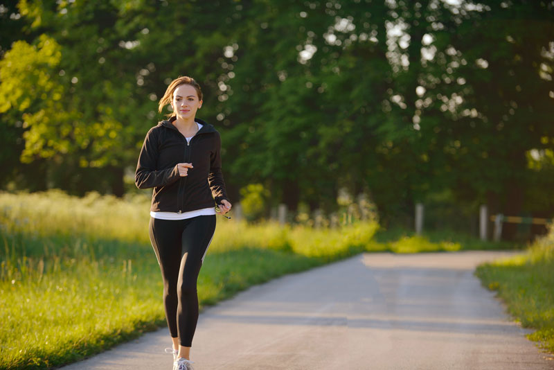 woman running in black hoodie outside on trail