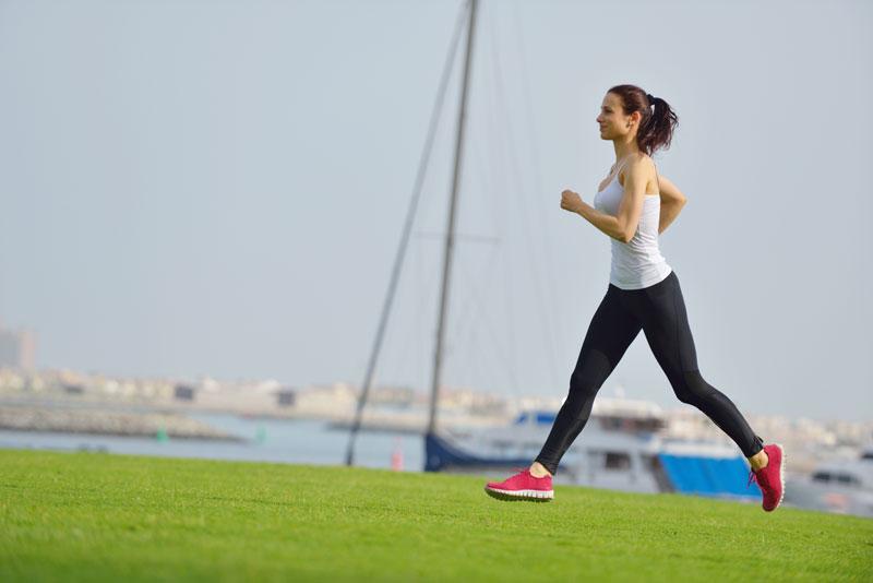 girl running outside on grass