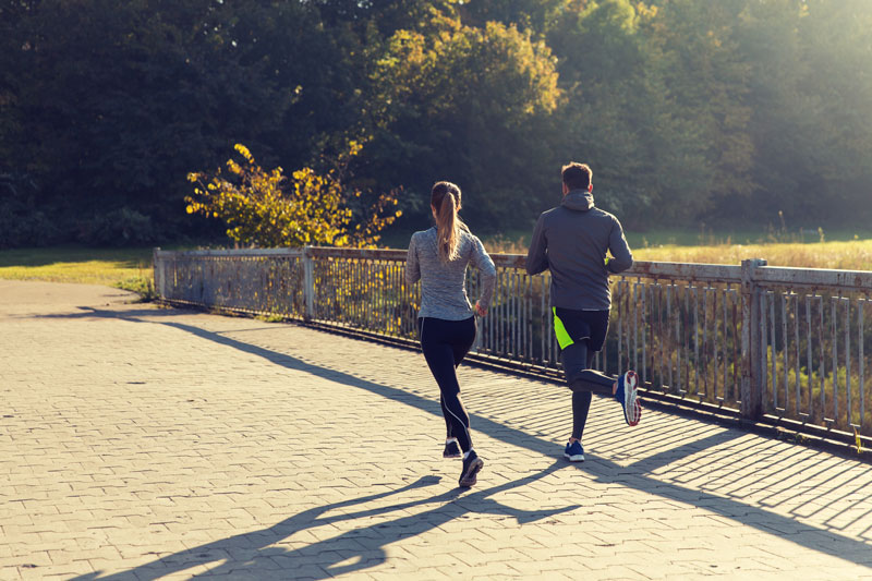 man and woman running together outside on bridge