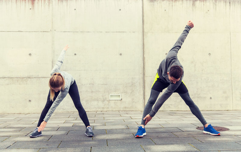 man and woman stretching outside after a run