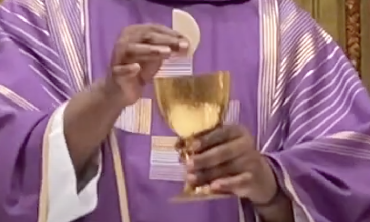 Father Paul's hands holding the Eucharist
