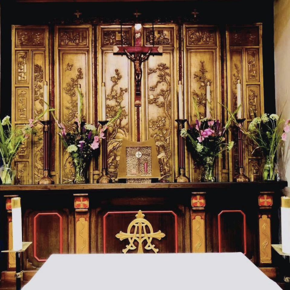 Altar of St. Benedict Parish, surrounded by candles and flowers, with a crucifix at the center