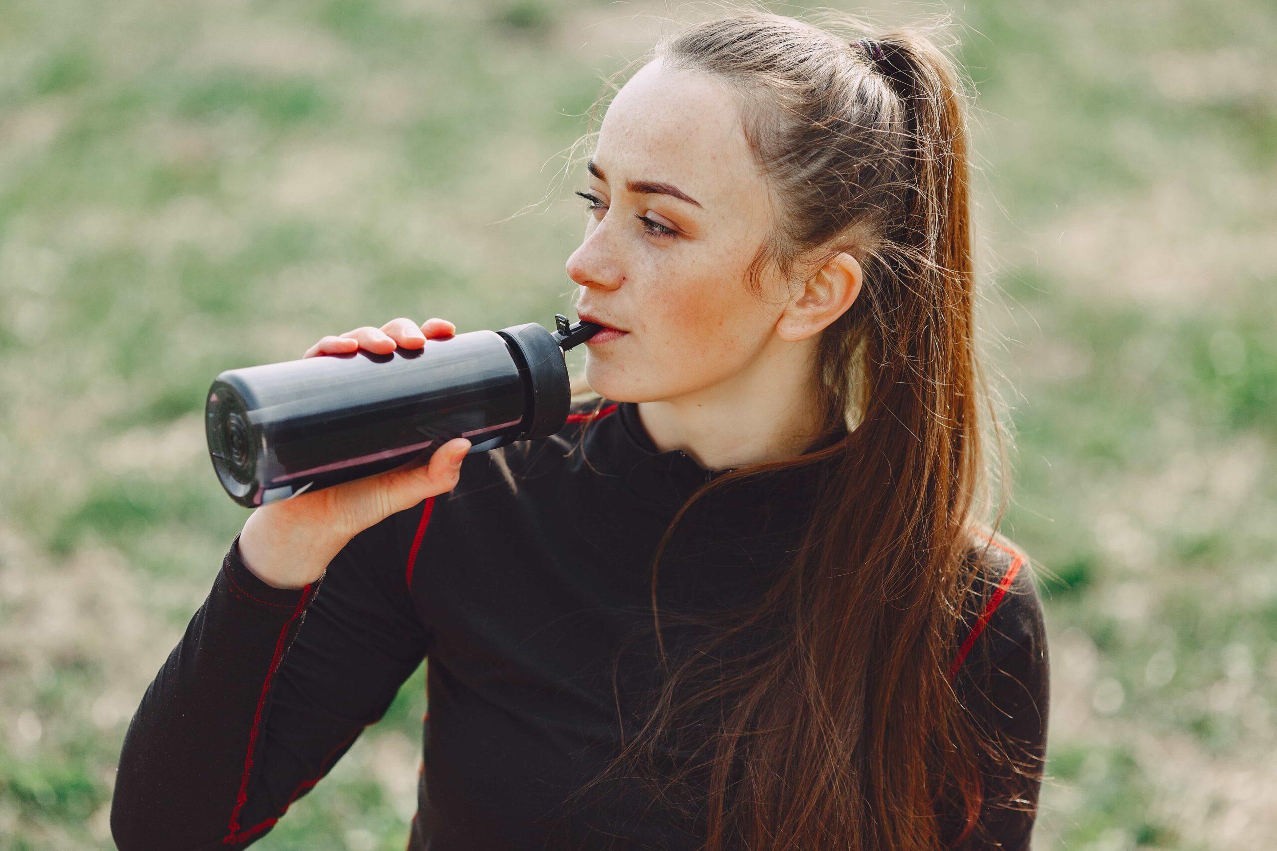 sportswoman-drinking-water-from-plastic-bottle-outdoors-4127318-min