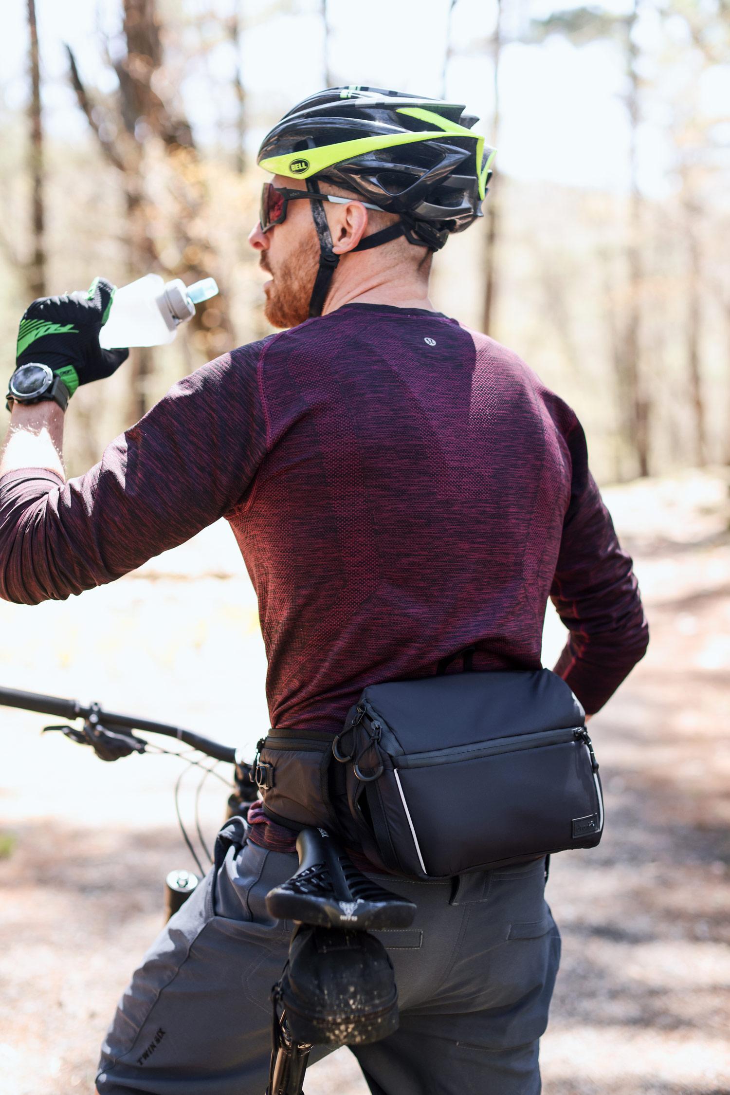 man mountain biking stopping for water