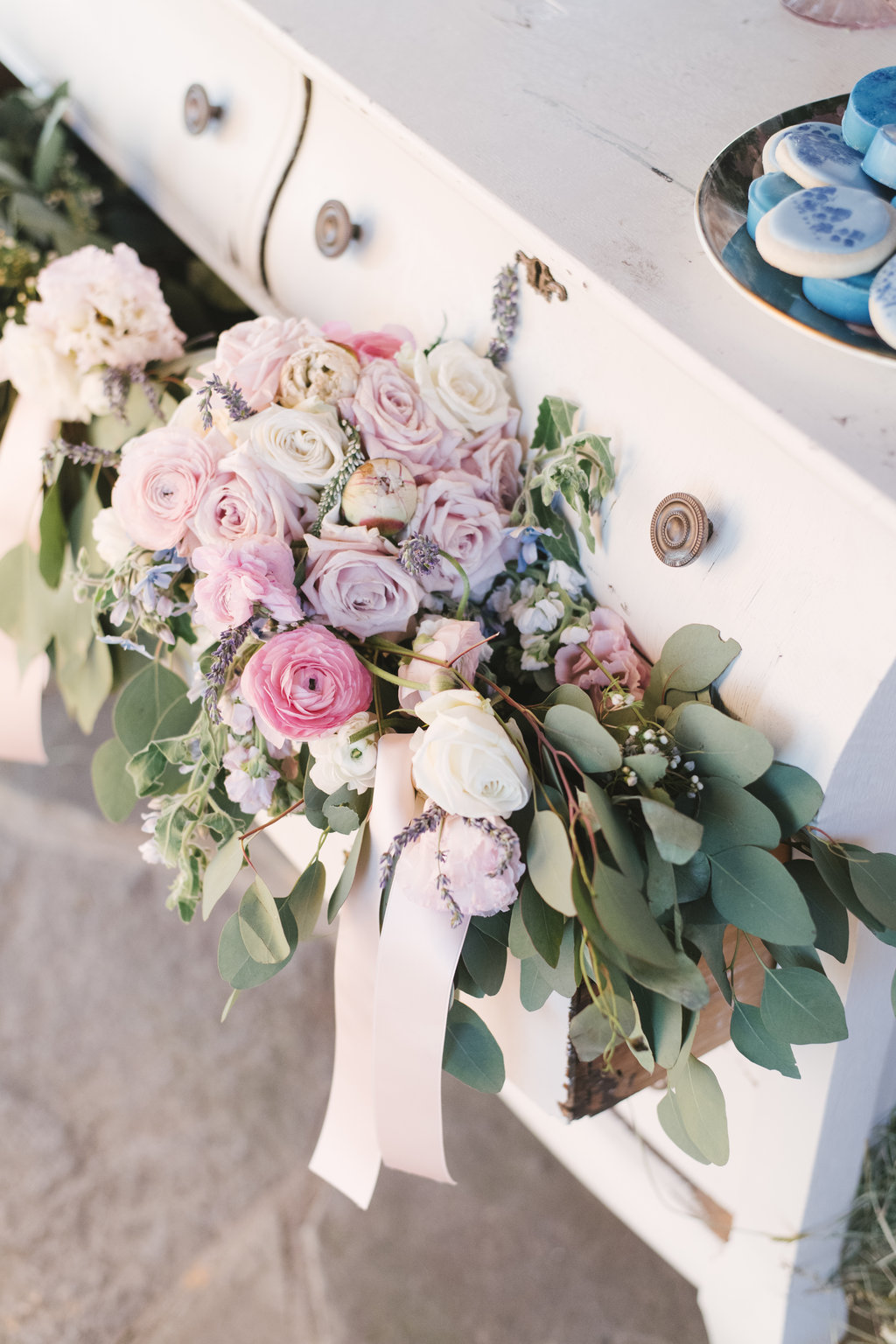 These pastel colors and greenery were gorgeous placed inside our vintage white dresser for this outdoor barn wedding we planned.
