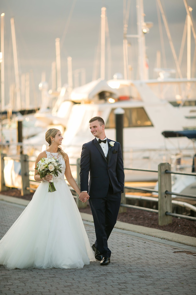 Our bride and groom looked so chic on their wedding day as they walked along the pier where dozens of boats were docked.
